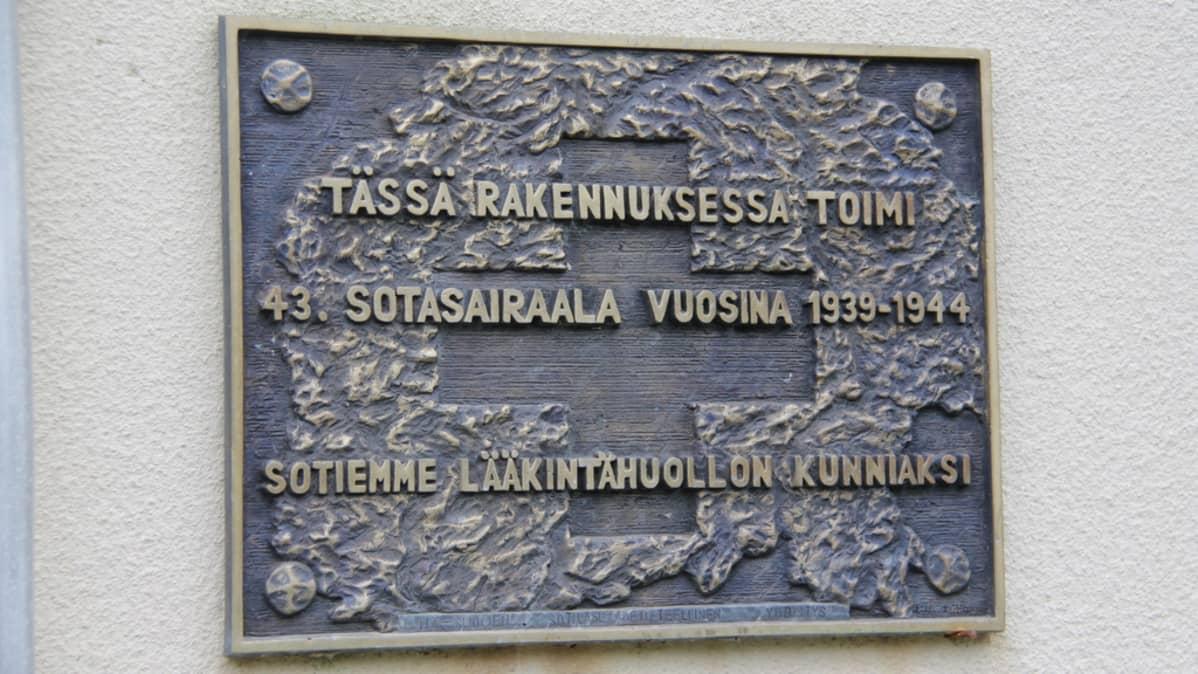 Muistolaatta Tiurun entisen sotilassairralan seinällä