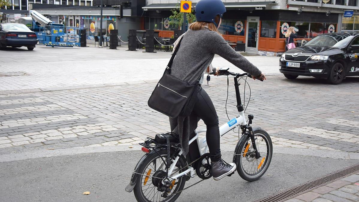 Nainen pyöräilee sähköpolkupyörällä kadulla