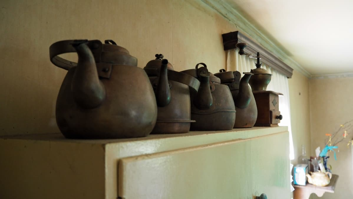 vanhoja kahvipannuja rivissä