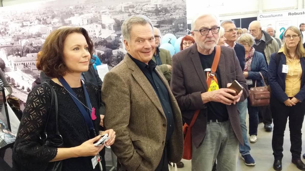 Ohjelmapäällikkö Jenni Haukio, tasavallan presidentti Sauli Niinistö ja ruokatoimittaja Markku Haapio messujen vilskeessä.