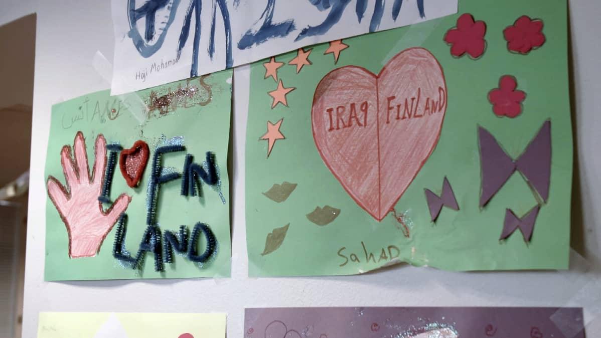 Turvapaikanhakijoiden piirustuksia vastaanottokeskusksen seinällä.