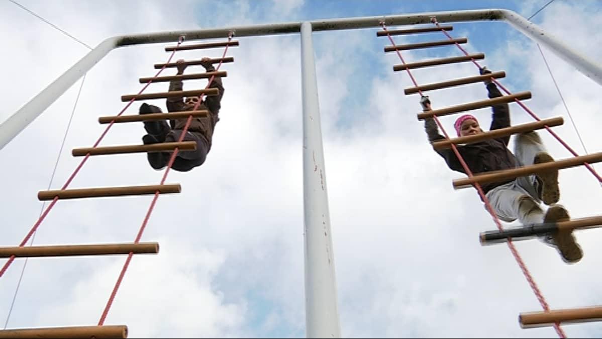 Kaksi tyttöä kiipeää viisi metriä korkeita köysitikkaita