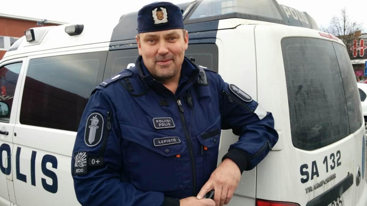 Poliisi seisoo poliisiauton edessä.
