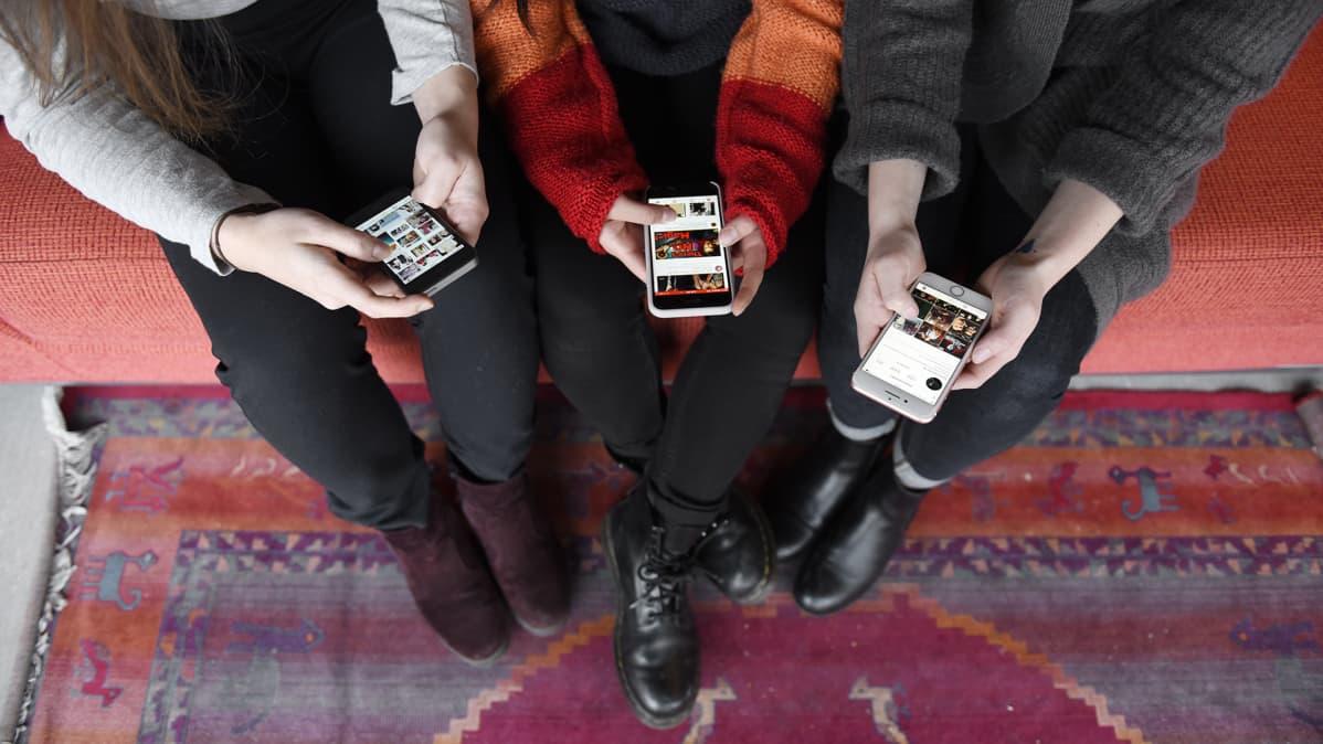 Nuoret tutkivat kännyköitään.
