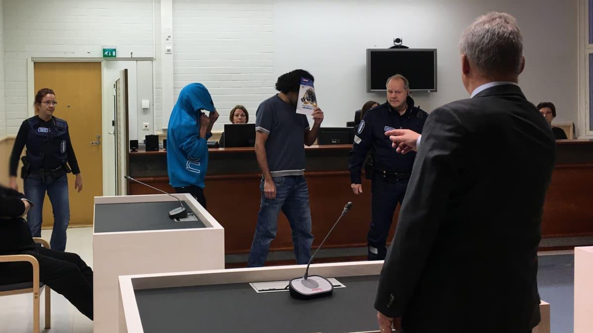 Otanmäen taposta syytetyt peittivät kasvonsa oikeudessa.