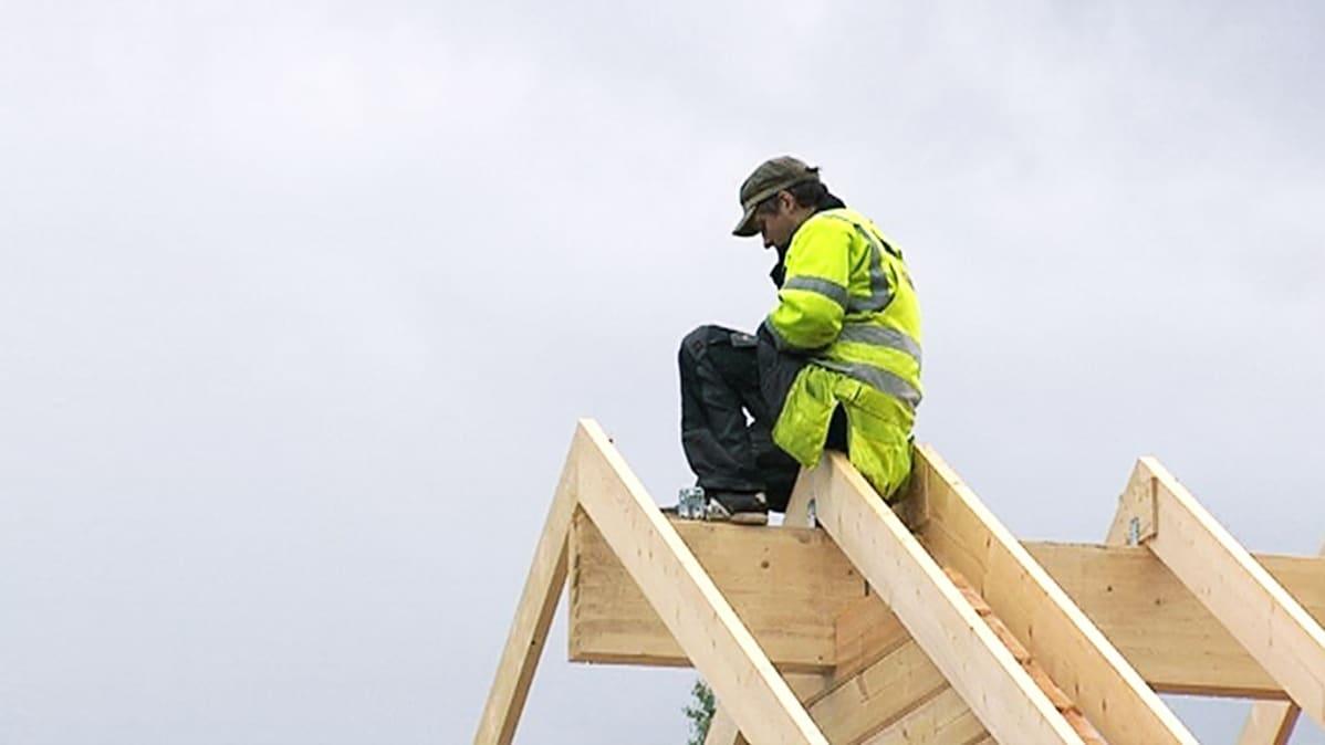 Rakennusmies istuu talon katonharjalla