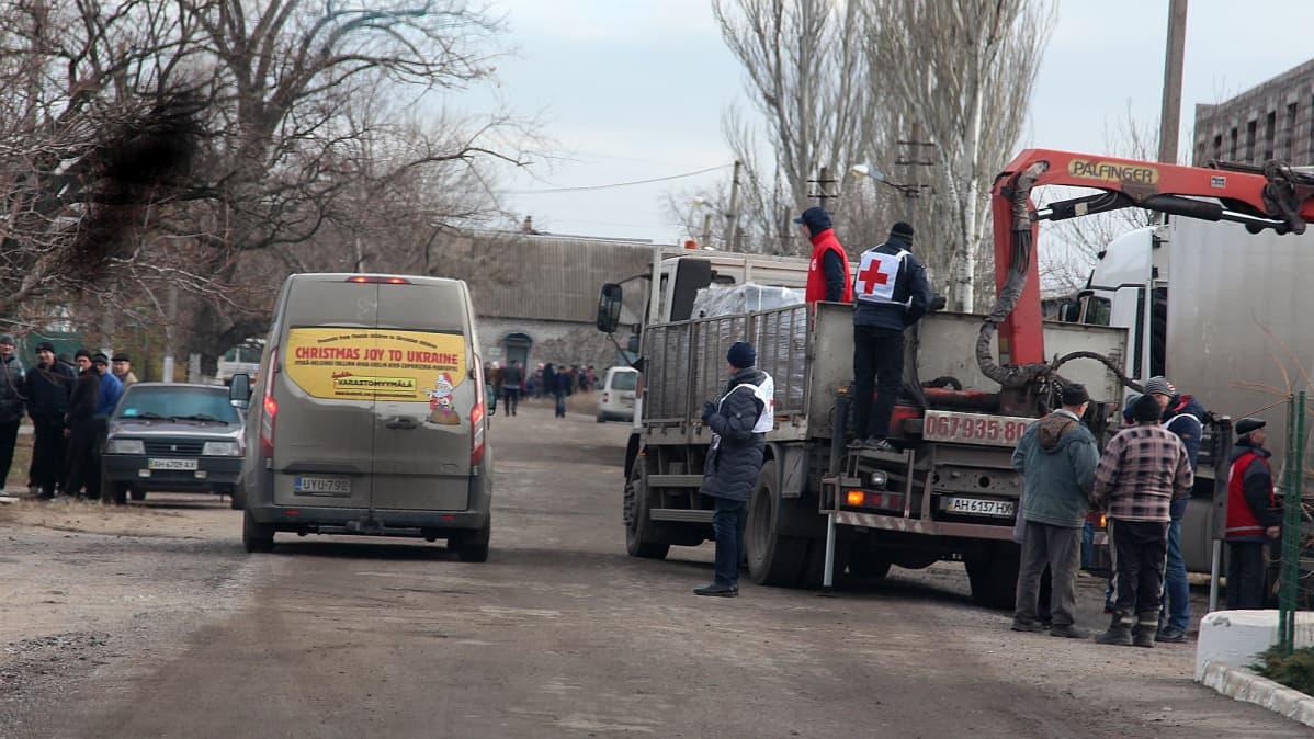 Kaksi kilometriä rintamalle. Pakettiauton vieressä Punaisen Ristin rekasta puretaan puupellettejä Mariupolin asukkaille viime joulun alla.
