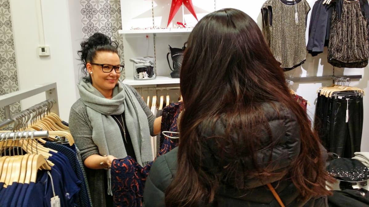 Kuvassa myyjä esittelee asiakkaalle vaatetta