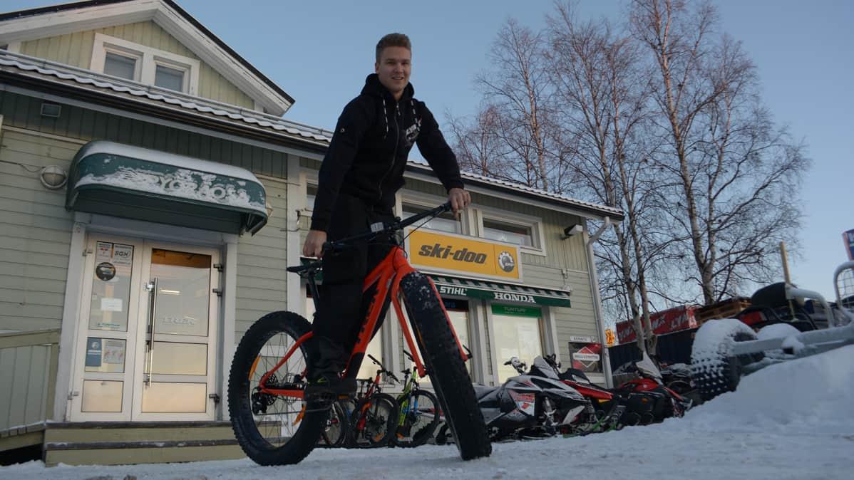Arto Keinänen seisoo pyörän päällä pyöräliikkeensä edessä Torniossa.