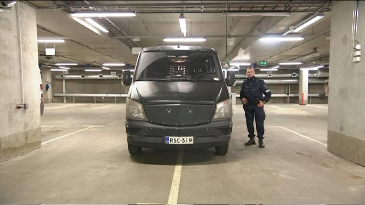 """Ylikonstaapeli Harri Perälä ja """"Mörkö"""", eli poliisin joukkojenhallintaan tarkoitettu erikoissuojattu kulkuneuvo. Auto on päällystetty muovilevyillä, jotka suojaavat sitä esimerkiksi kivien ja pullojen osumilta."""