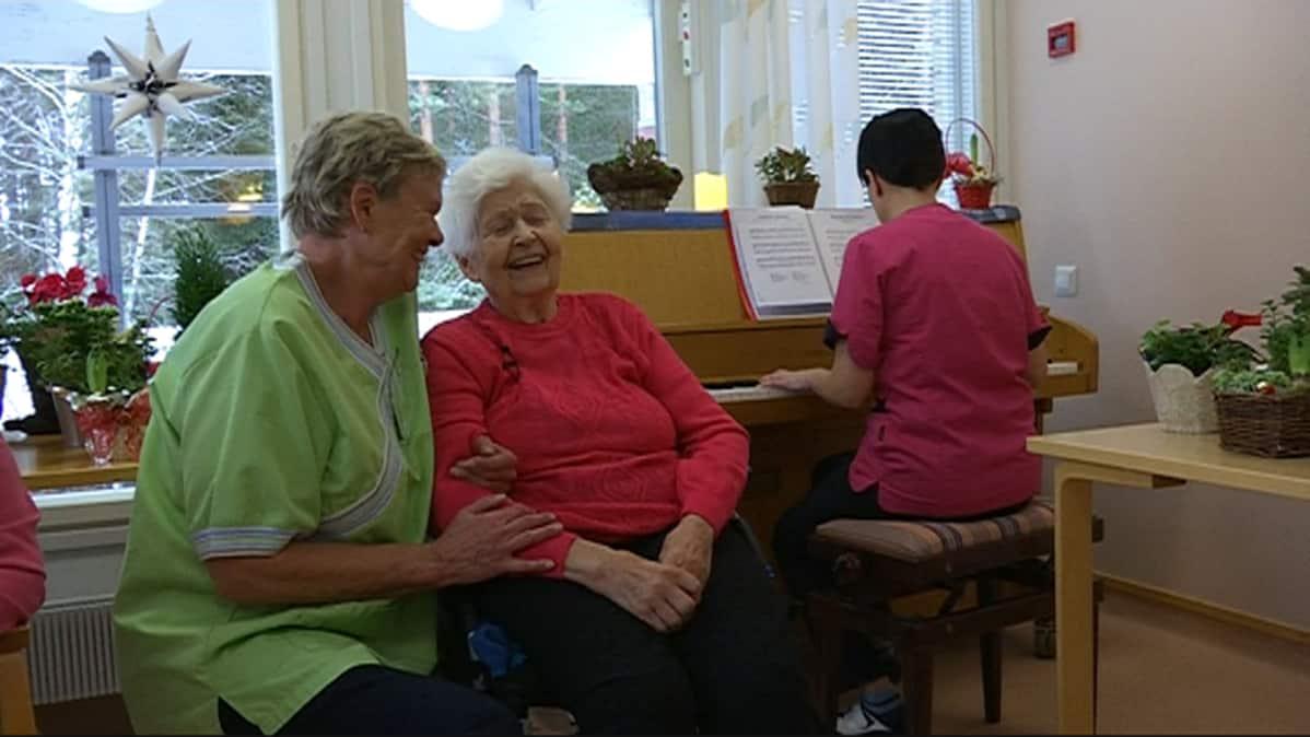 Kirsti Lehmunen nauttii musiikista hoitajien kanssa.