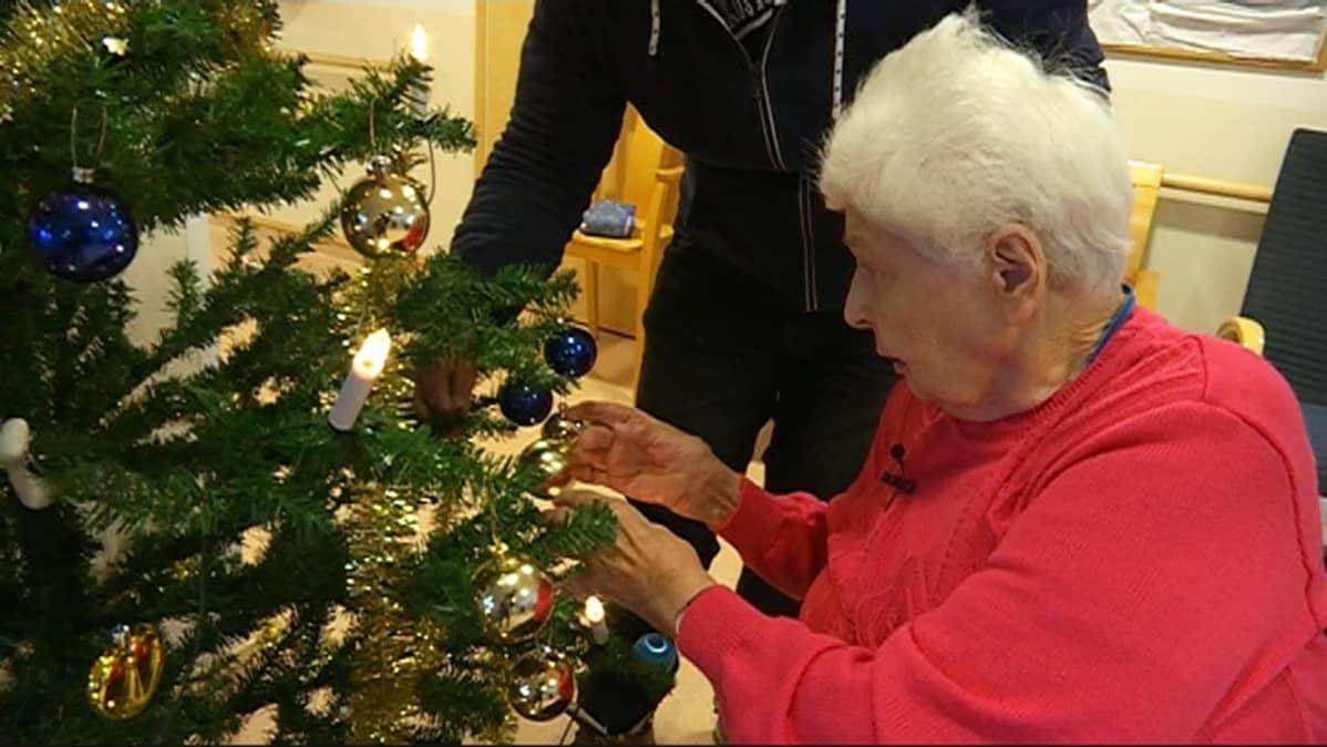 Kirsti Lehmunen asettelee joulukoristeita paikalleen hoivakoti Muuraskodissa.
