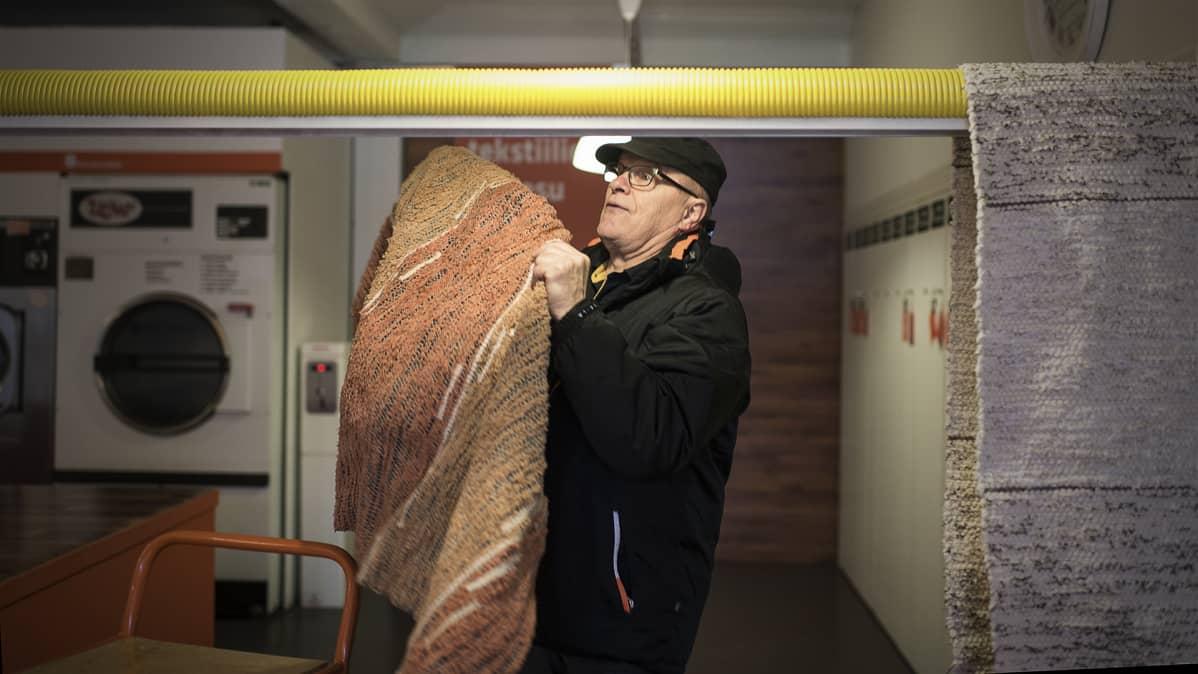 Reijo Meriläinen ripustaa mattoja kuivumaan.