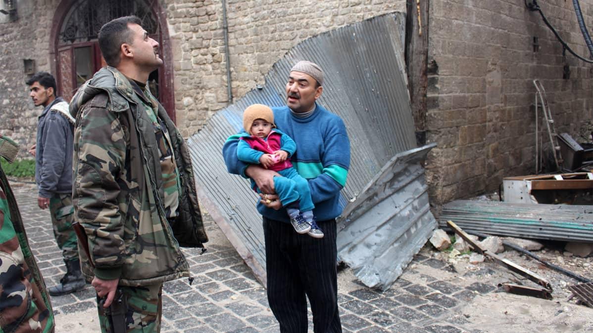 Maastopukuun pukeutunut henkilö ja siviilivaatteisii pukeutunut mies kantaa lasta.