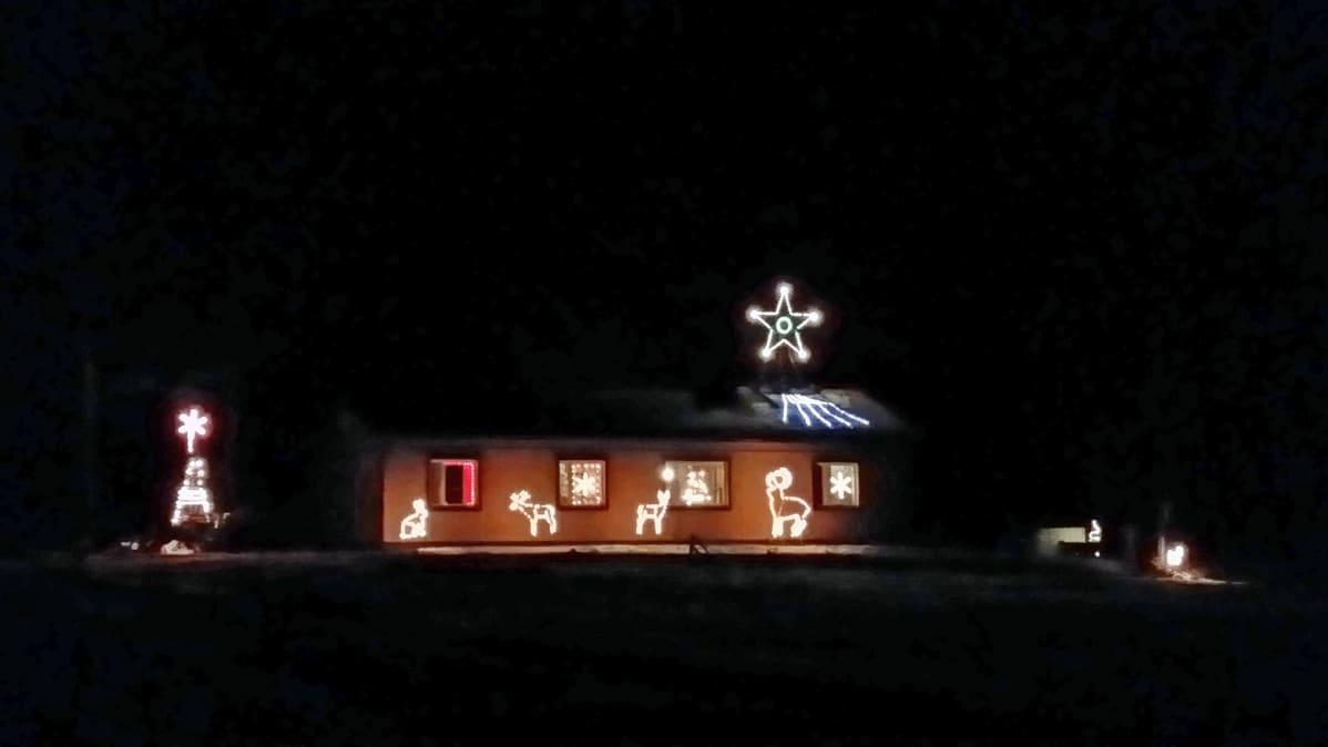 Kuvassa jouluvaloin koristeltu talo, joka loistaa pimeässä