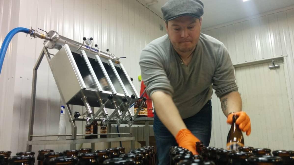 Mies siirtää kaljapulloja.