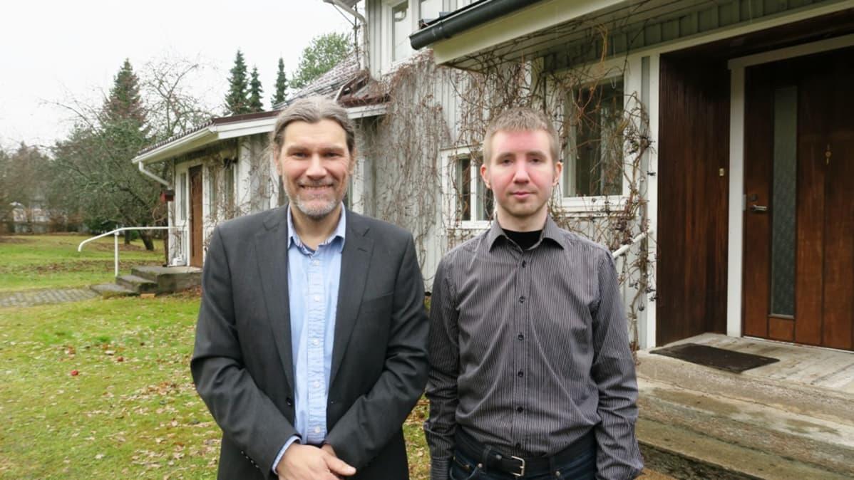 Kaksi miestä seisoo talon edessä.