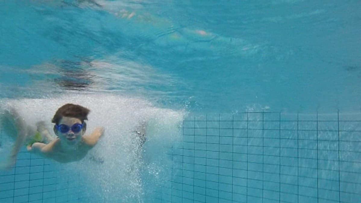 Lapsi sukeltaa Kinnulan uimahallissa.