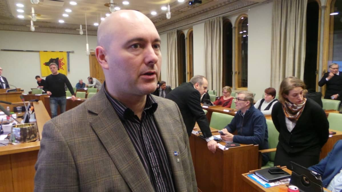 Mies seisoo etualalla. Taustalla valtuustosali ja ihmisiä. Ari Jalonen Porin kaupunginvaltuutettu kansanedustaja perussuomalaiset.
