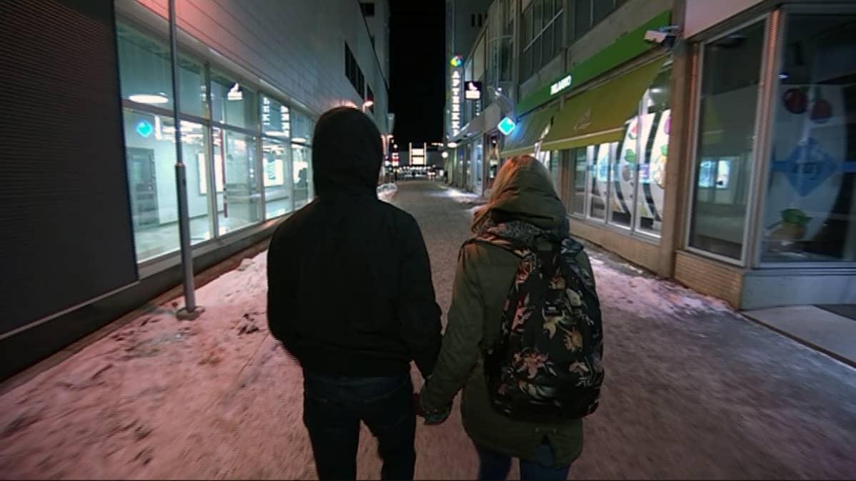 Kaksi nuorta kävelee kadulla talvi-iltana.