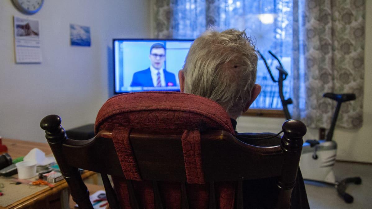 78-vuotias Paavo Karjalainen katsoo televisiota kotonaan Hyrynsalmella.