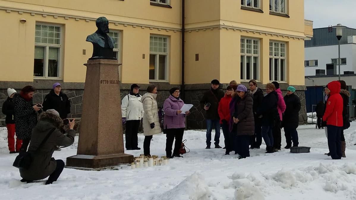 Kuvassa hoitajia on kokoontunut kynttilämielenilmaukseen Otto Malmin patsaalle Pietarsaaren sairaalalla