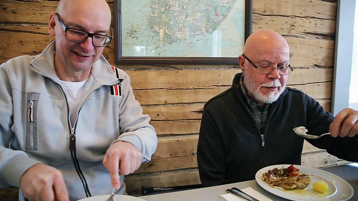 Jari Peltola ja Antero Pääjärvi istuvat pöydän ääressä ja syövät lounasta.