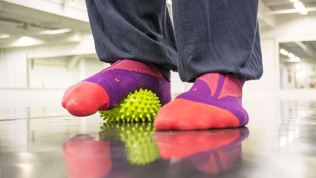 Tanssijan jalkapohja hierovan pallon päällä.
