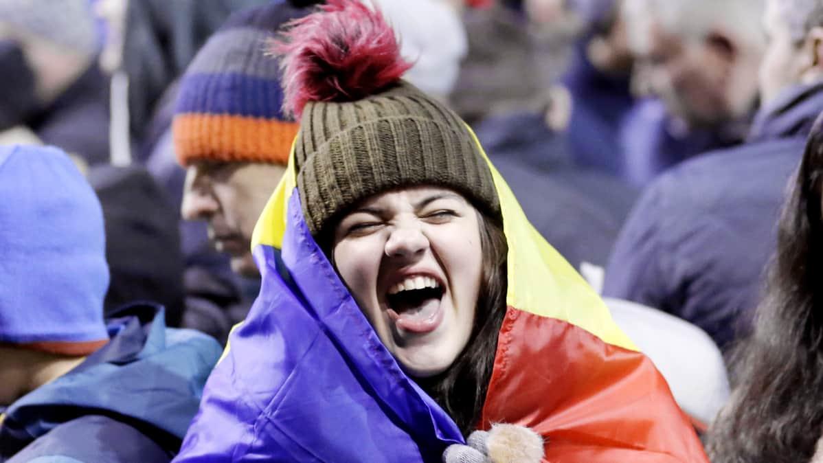 Romanialainen nuori nainen osoittaa mieltään Bukarestissa.