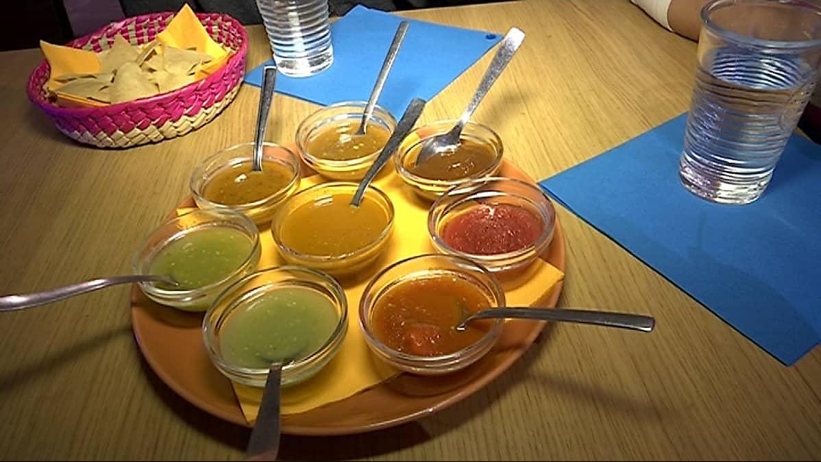 Seitsemän erilaista salsakastiketta meksikolaisessa ravintolassa.