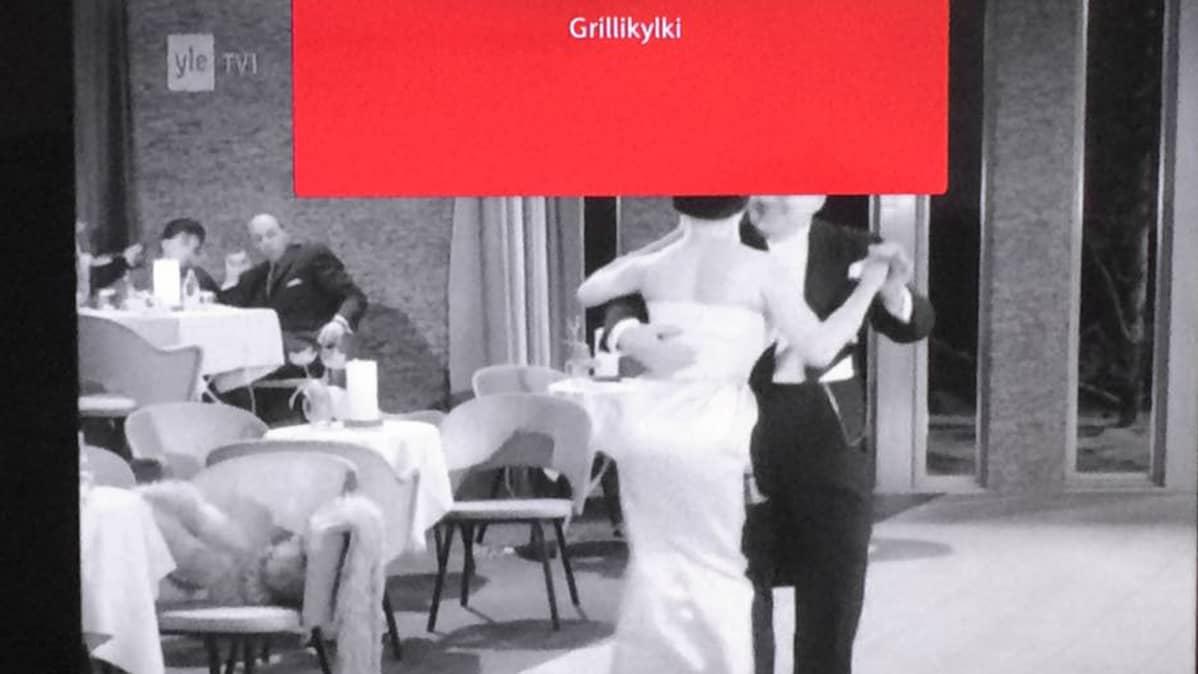 """Tv-kuva, jossa näkyy teksti """"grillikylki"""" sekä kuvassa tanssijoita."""