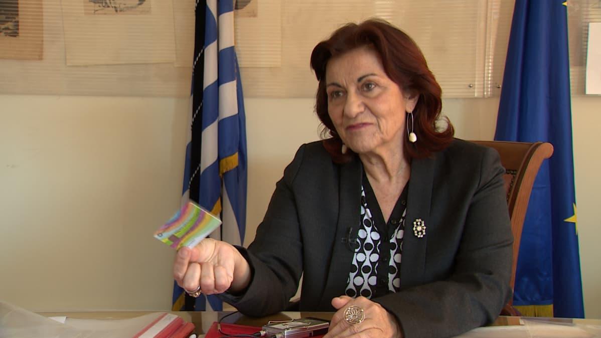 Kreikan sosiaaliministeri Theano Fotiou esittelee pankkikorttia, jollaisen avulla kreikkalaisille jaetaan toimeentulotukea. Kortti otettiin käyttöön vasemmistolaisen Syriza-puolueen valtakaudella.