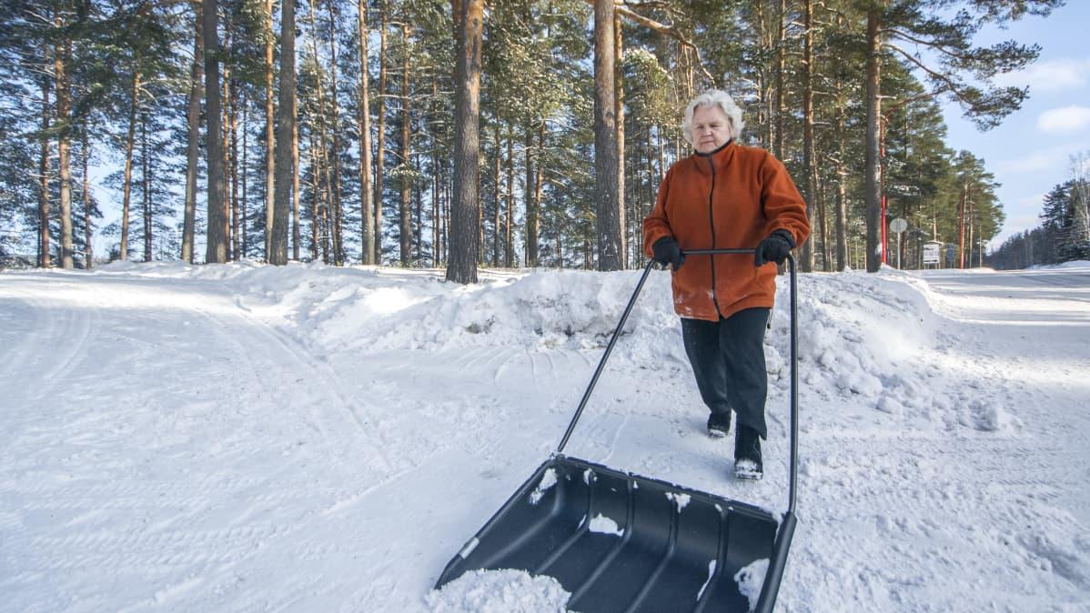 Nainen kolaa lunta.