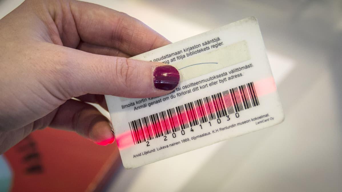 Kirjastokortin viivakoodia luetaan lukijalla.