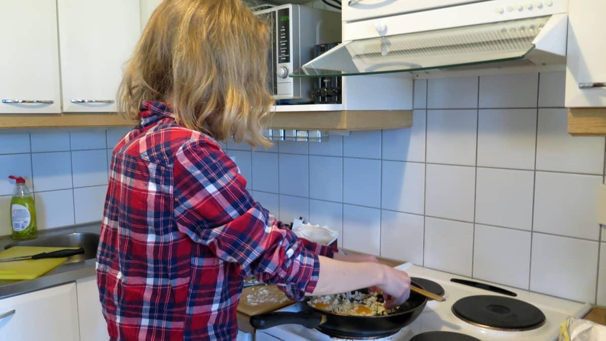 Nuori laittaa kasvisruokaa