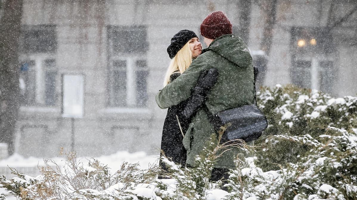 Nainen ja mies halaavat lumisateessa.