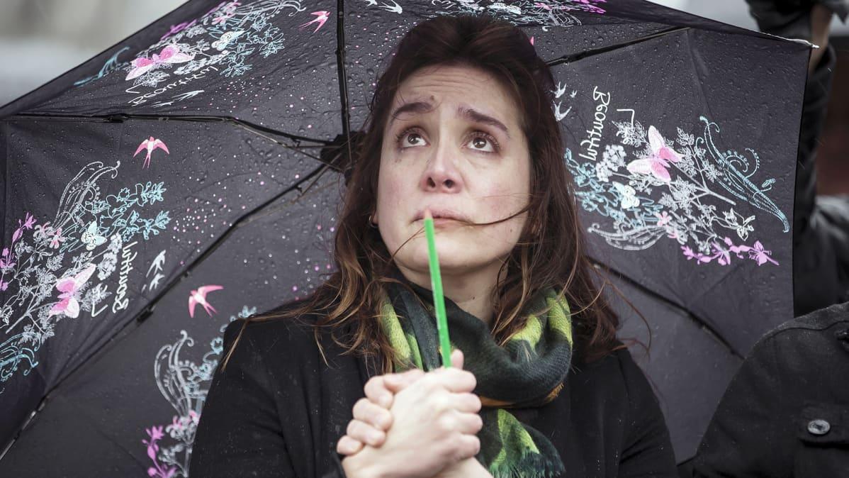 Nainen itkee sateenvarjon alla.
