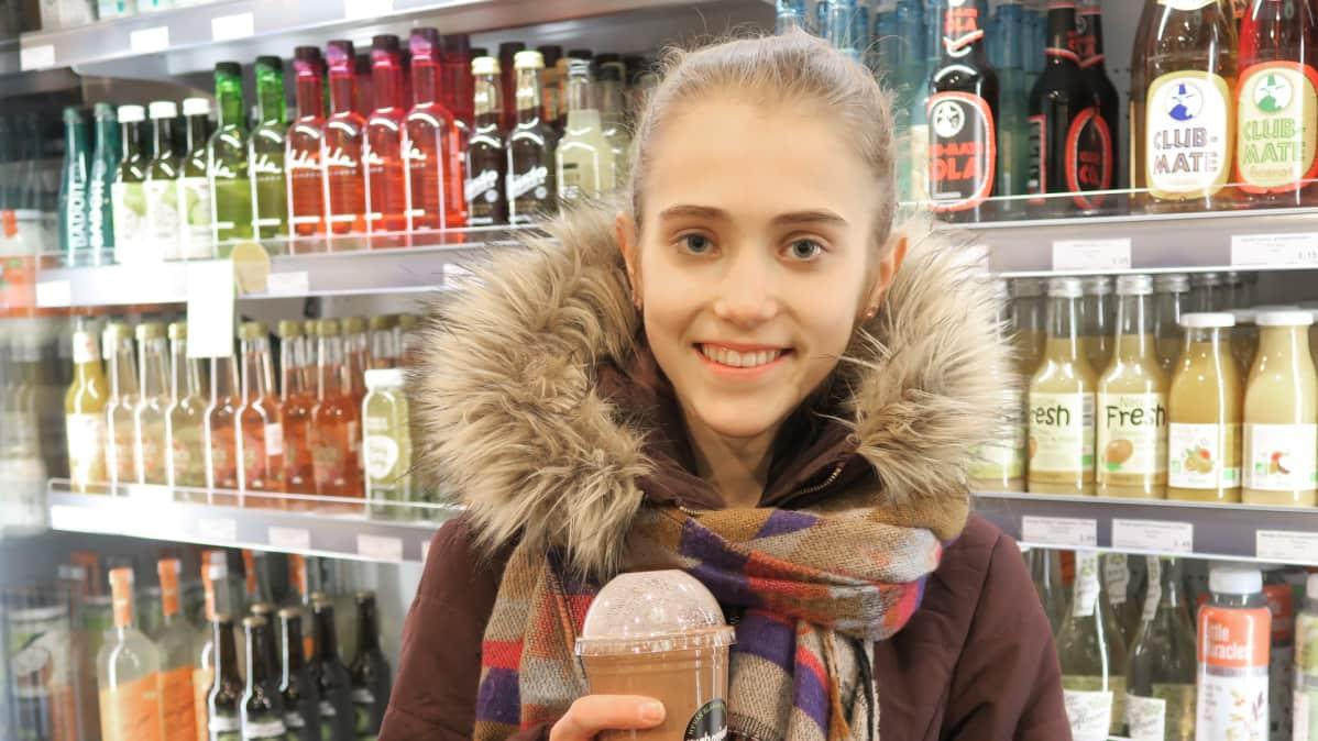 Hanna Ahola seisoo kaupassa juomahyllyn edessä.