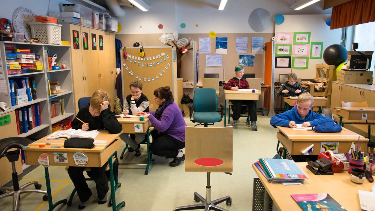 Erityislapsia opiskelemassa koululuokassa.