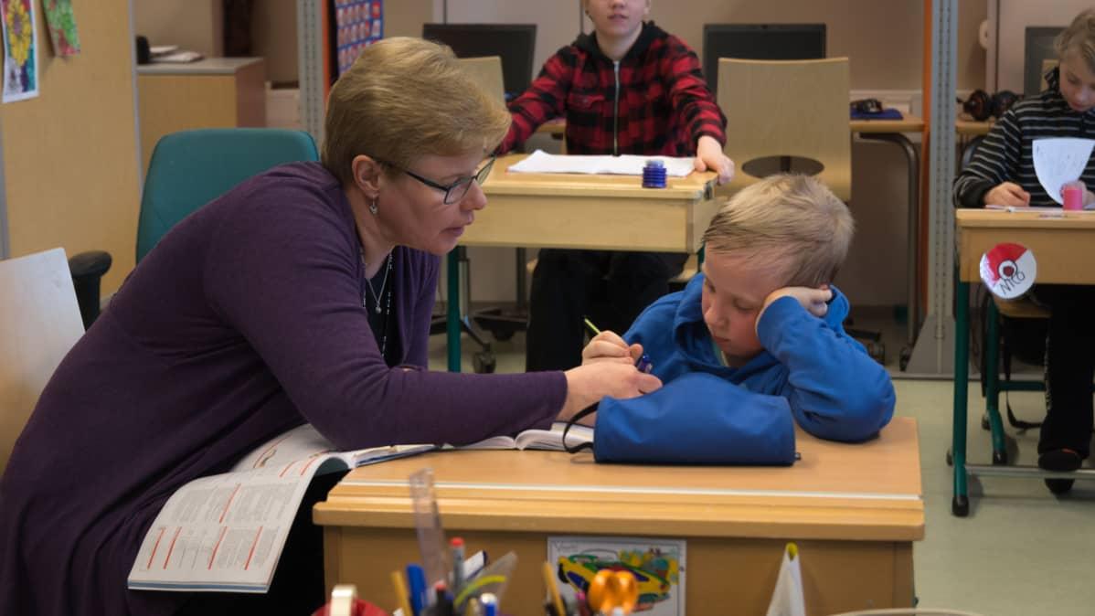 Erityisluokanopettaja Tarja Leinonen opastaa Veeti Saarenpäätä koulutehtävässä.