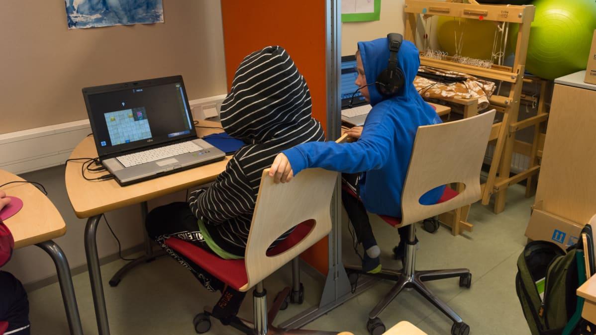 Kaksi koululaista pelaa tietokoneilla.