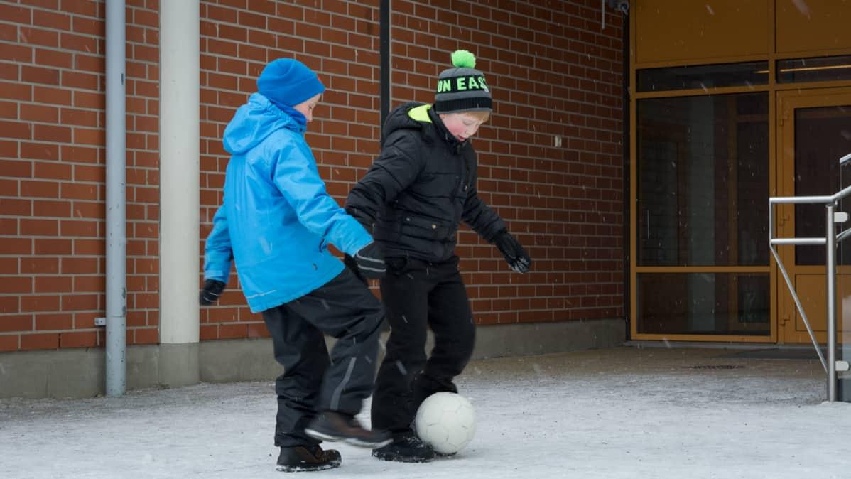 Kaksi koululaista pelaa jalkapalloa välitunnilla.