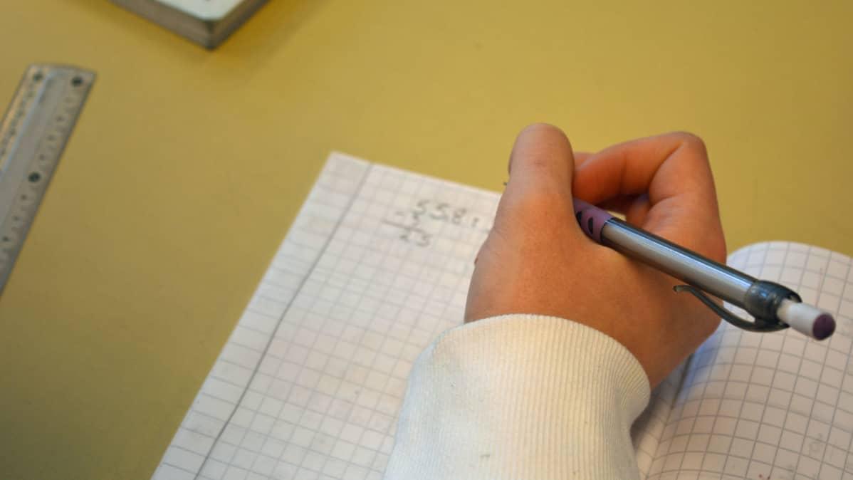 Oppilas tekee matematiikan tehtävää vihkoon.
