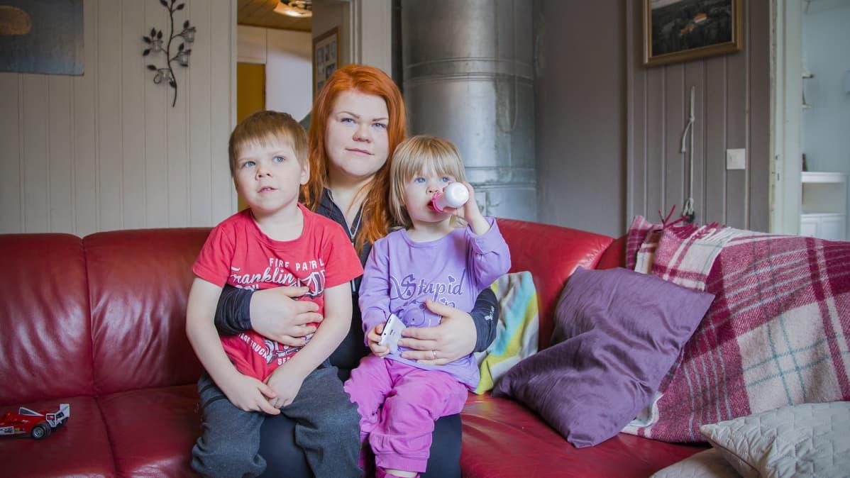 Mirka Koskela ja lapset Jomi ja Kerttu istuvat sohvalla