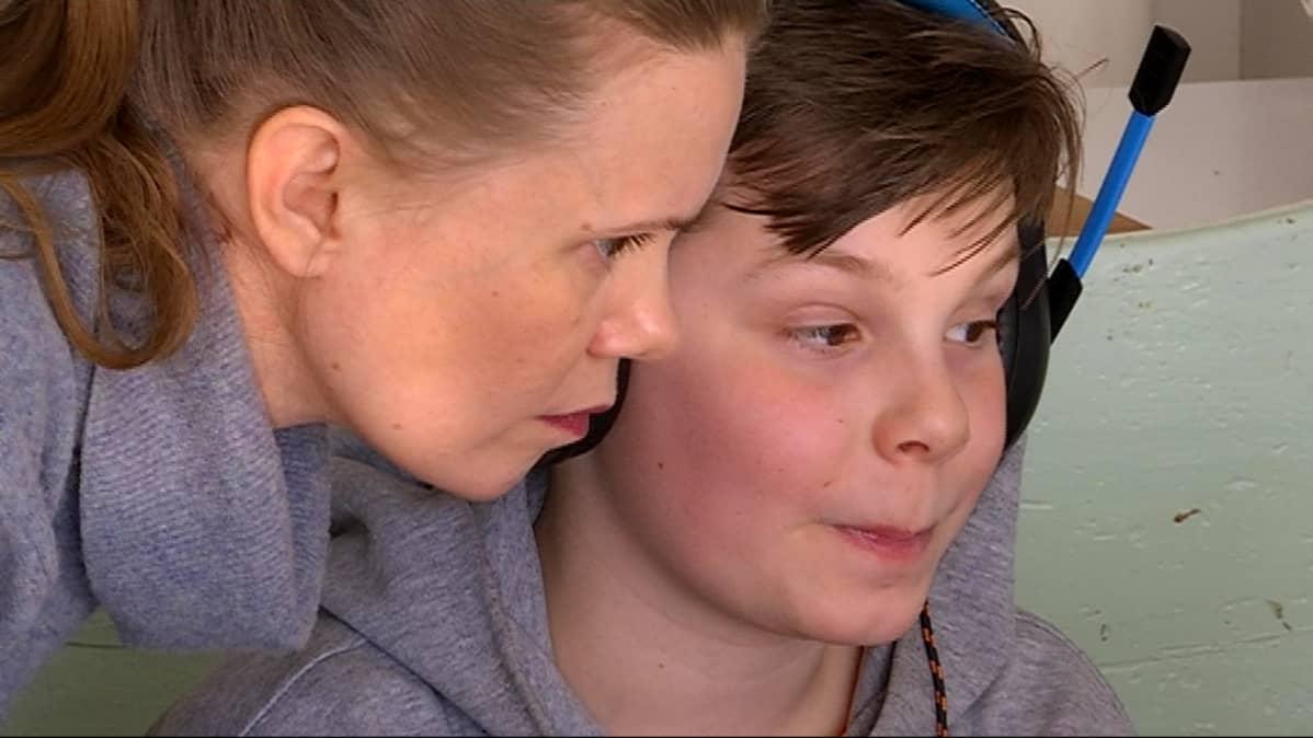 Karoliina Juhola auttaa poikaansa Mihku Näkkäläjärveä etätunnilla ilmaantuneissa teknisissä ongelmissa.