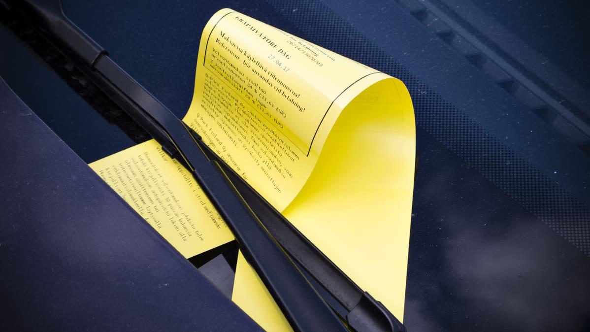 Keltainen parkkisakko tuulilasinpyyhkijän alla.