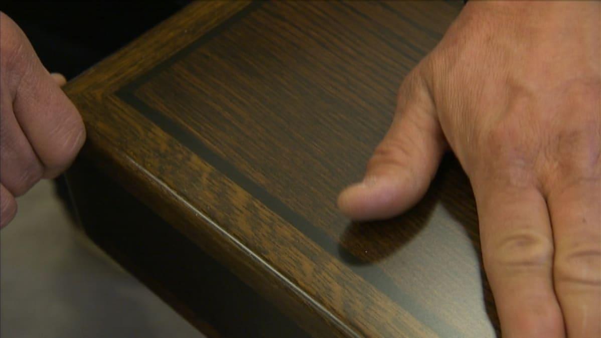 Eduskunnan 30-luvun pöytien kapea viiluraita on mustaksi petsattua päärynäpuuta, muu on valkotammea.