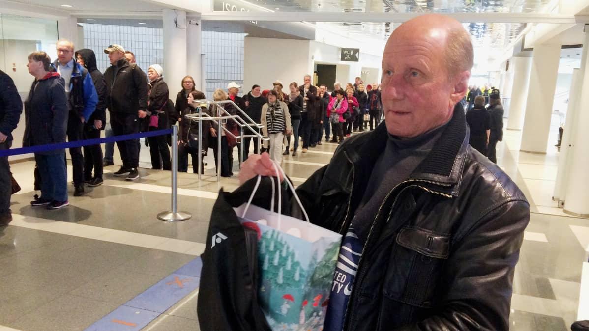 Mies pitää kädessään muumimukikassia Tampere-talon aulassa, taustalla kymmenien ihmisten jono