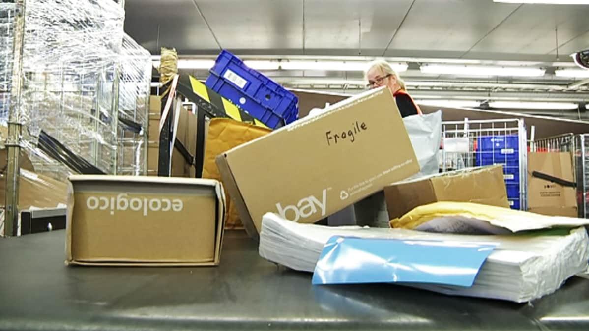 Paketteja Postin lajittelukeskuksessa.