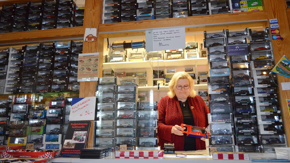 Leila Suutarinen kioskissa pienoismallien ympäröimänä.